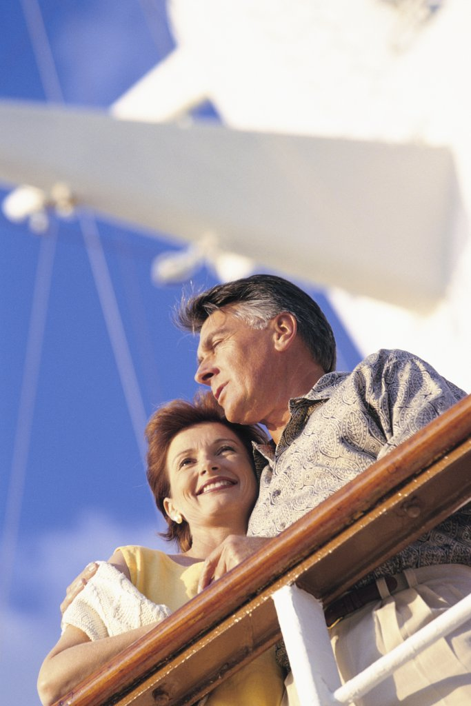 Stock Photo: 1574R-01349 Low angle view of a couple standing against the railing of a ship