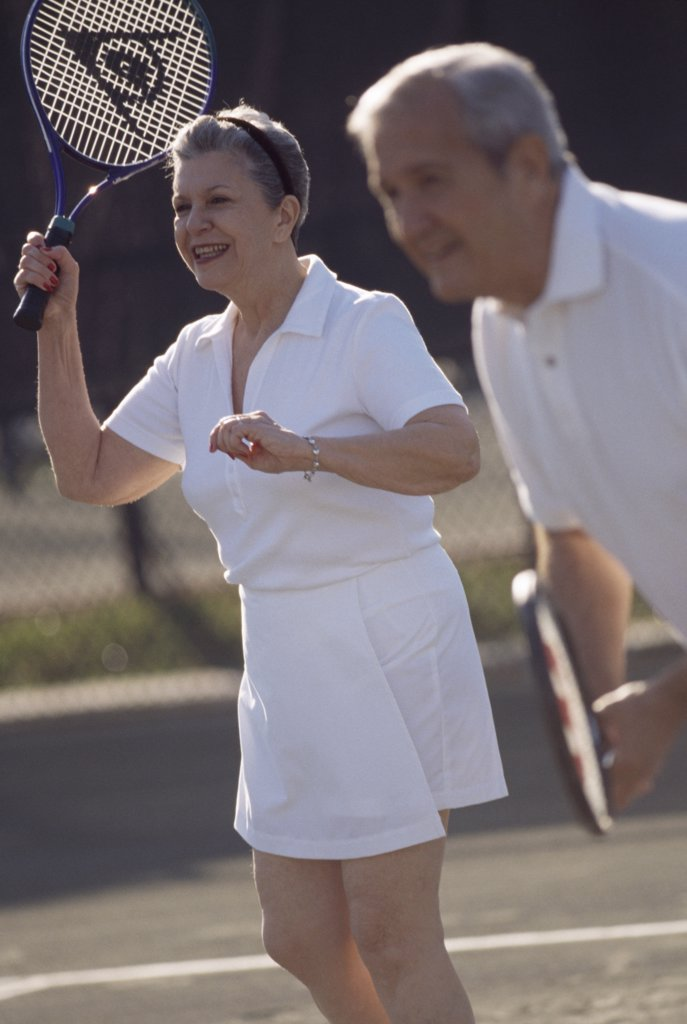 Stock Photo: 1574R-013531 Senior couple playing tennis