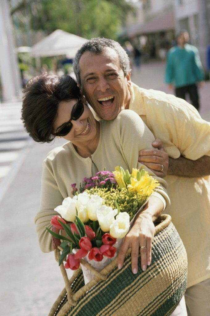Portrait of a couple smiling holding a bouquet of flowers : Stock Photo