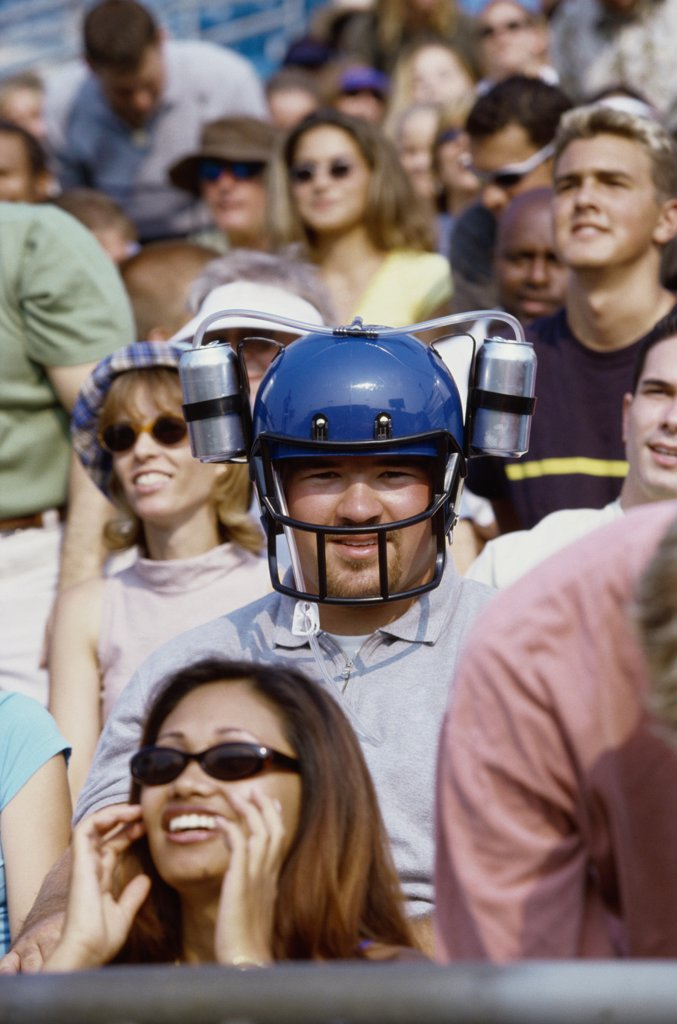 Portrait of a spectator wearing a football helmet : Stock Photo