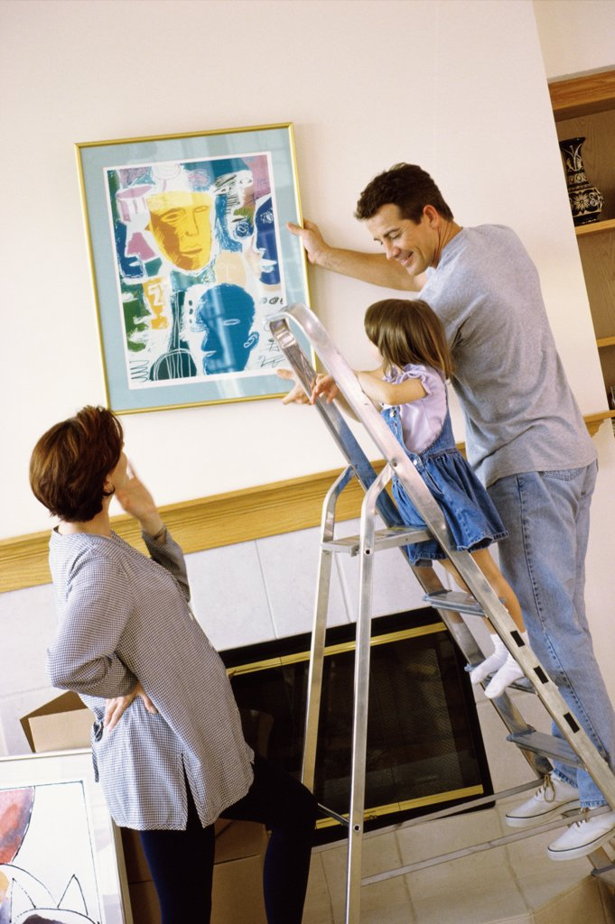 Father and daughter hanging a painting on the wall : Stock Photo