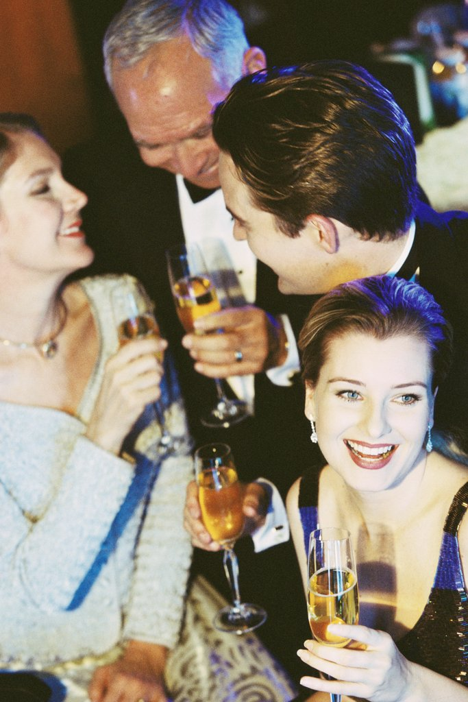 High angle view of a young couple and senior couple holding glasses of champagne at a bar : Stock Photo