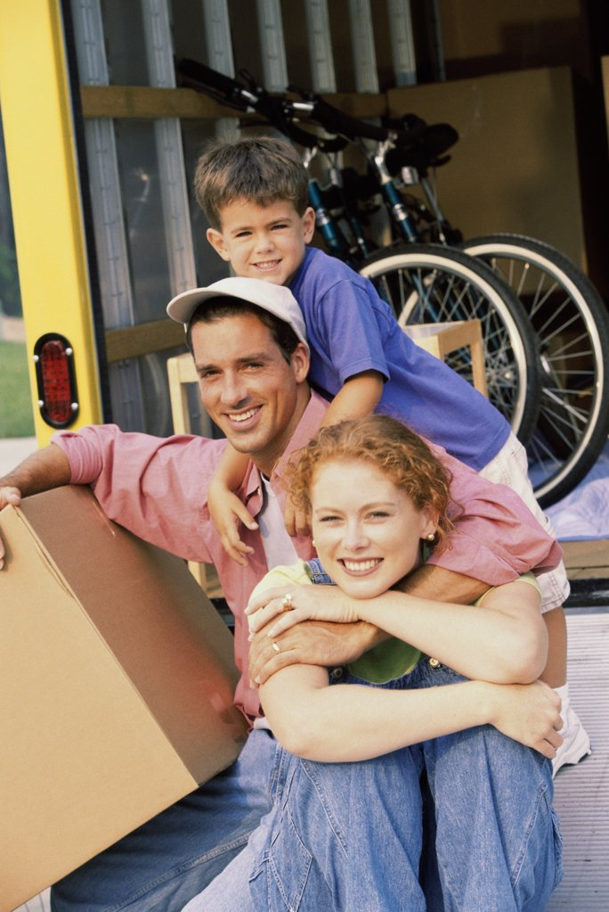 Portrait of parents with their son in their new home : Stock Photo