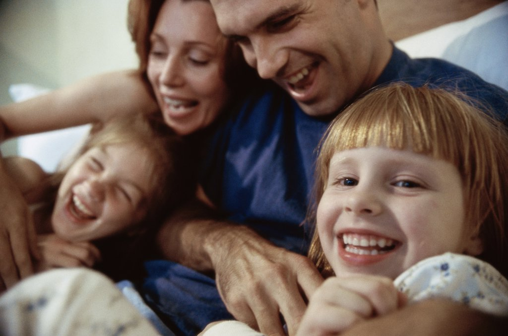 Close-up of parents and their two children playing in bed : Stock Photo