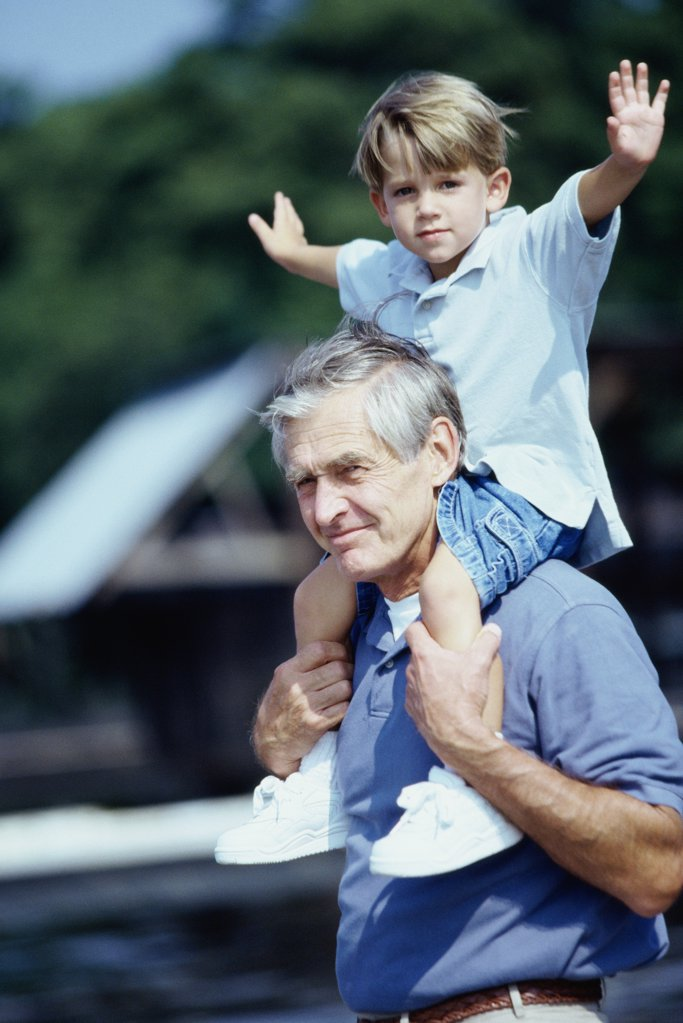 Side profile of a grandfather carrying his grandson on his shoulders : Stock Photo