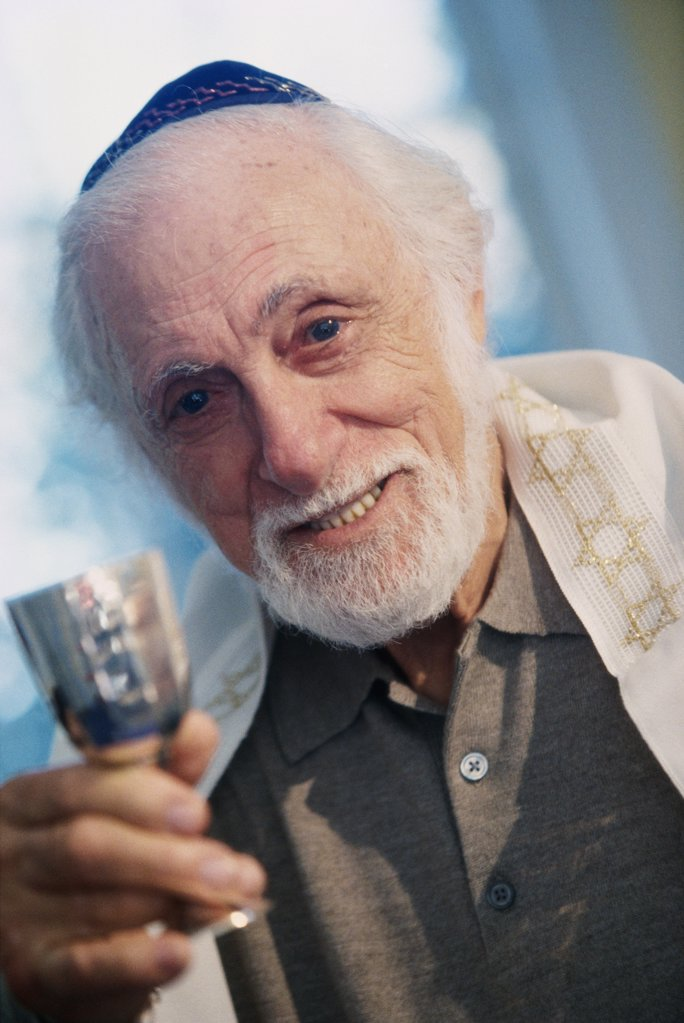 Portrait of a senior man holding a goblet at a Hanukkah ceremony : Stock Photo