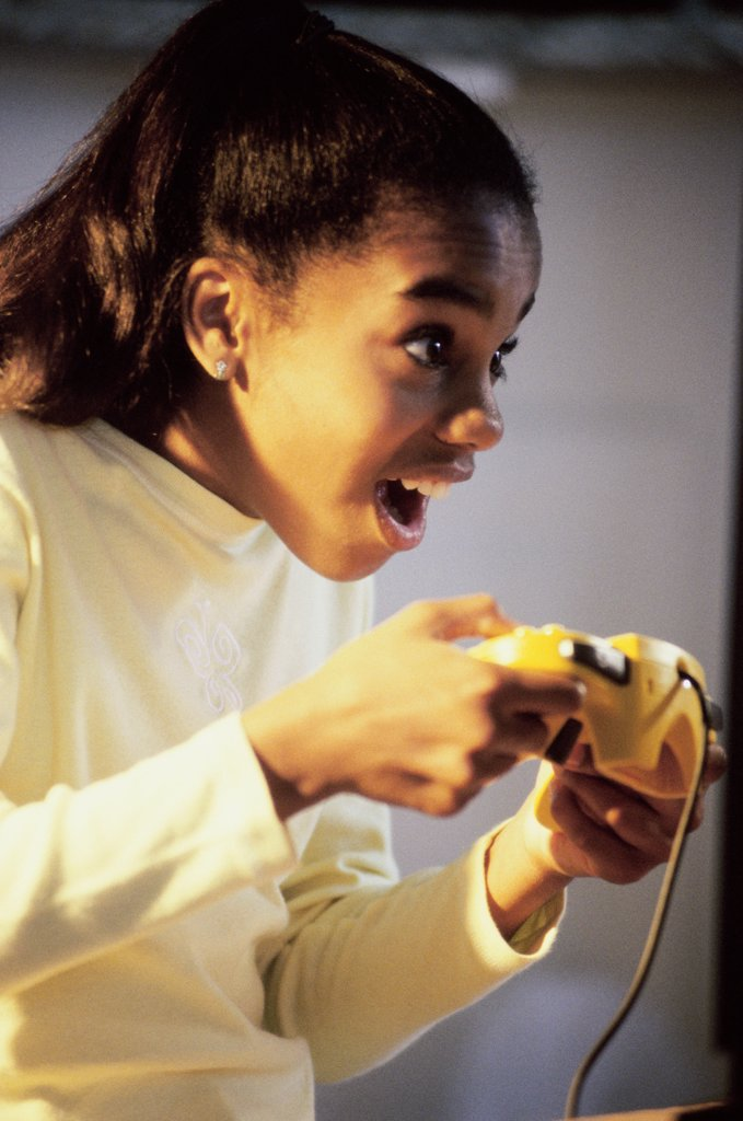 Side profile of a teenage girl playing video games : Stock Photo