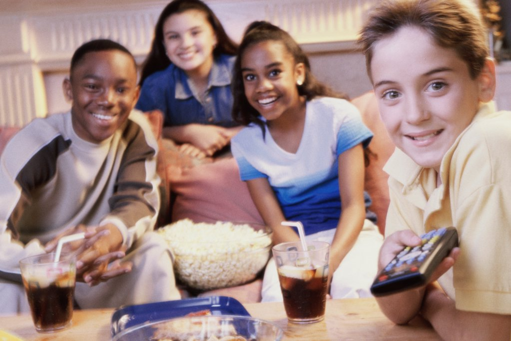 Two teenage girls and two teenage boys watching television : Stock Photo