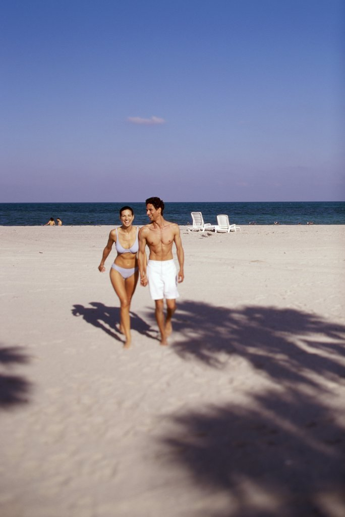Young couple walking on the beach : Stock Photo