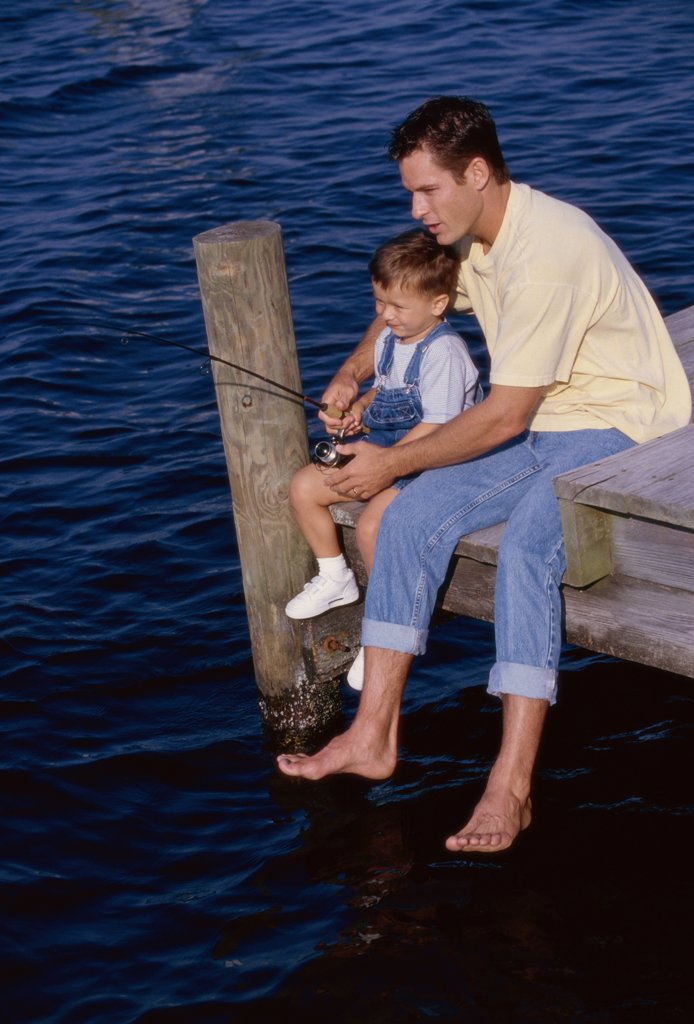 High angle view of a father teaching his son to fish : Stock Photo