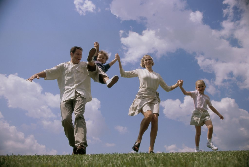 Low angle view of parents swinging their son : Stock Photo