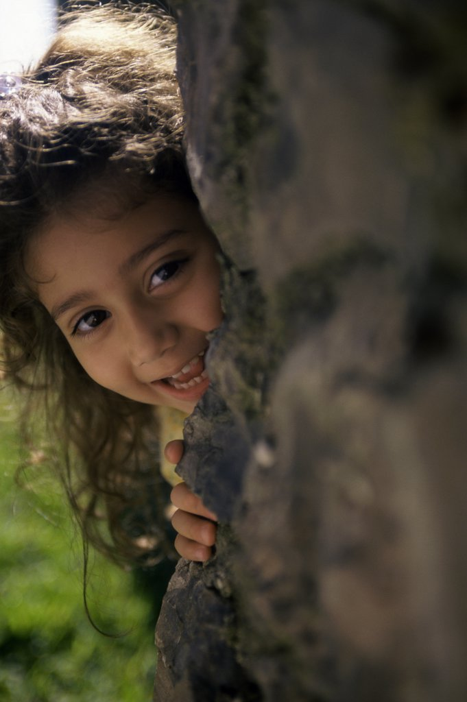 Portrait of a girl hiding behind a rock : Stock Photo