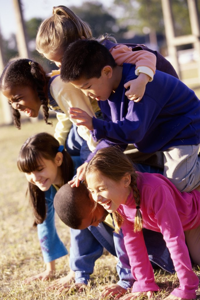 Stock Photo: 1574R-014743B Side profile of a group of children making a human pyramid