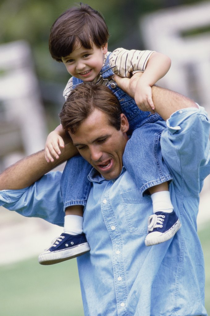 Father carrying his daughter on his shoulders : Stock Photo