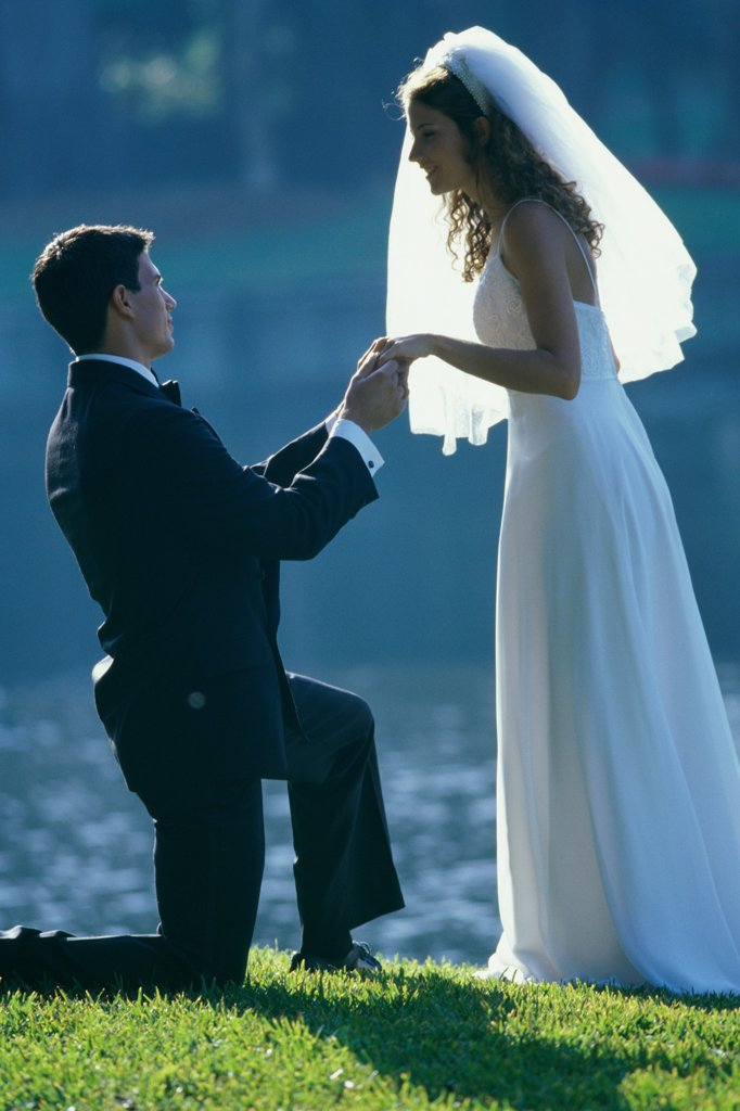 Side profile of a groom proposing to his bride near a lake : Stock Photo