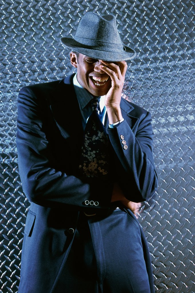 Businessman standing in front of a metallic wall laughing : Stock Photo