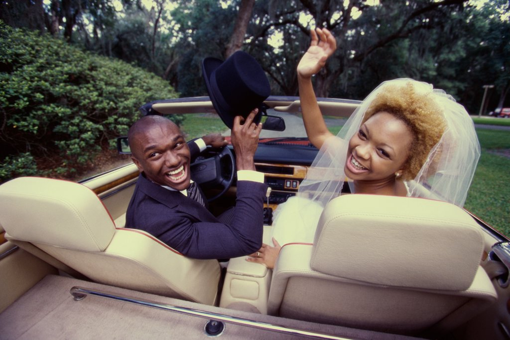 Rear view of a newlywed couple sitting in a convertible car : Stock Photo