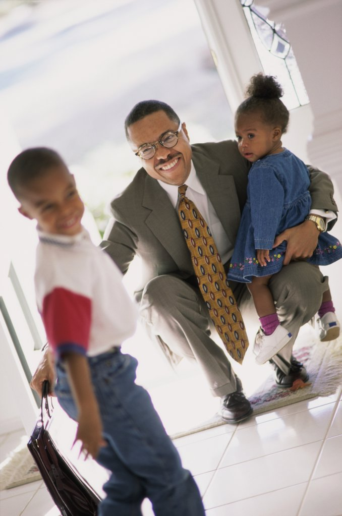 Businessman meeting his son and daughter at the door : Stock Photo