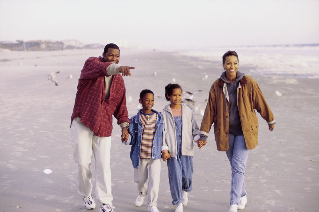 Parents and their two children walking on the beach : Stock Photo