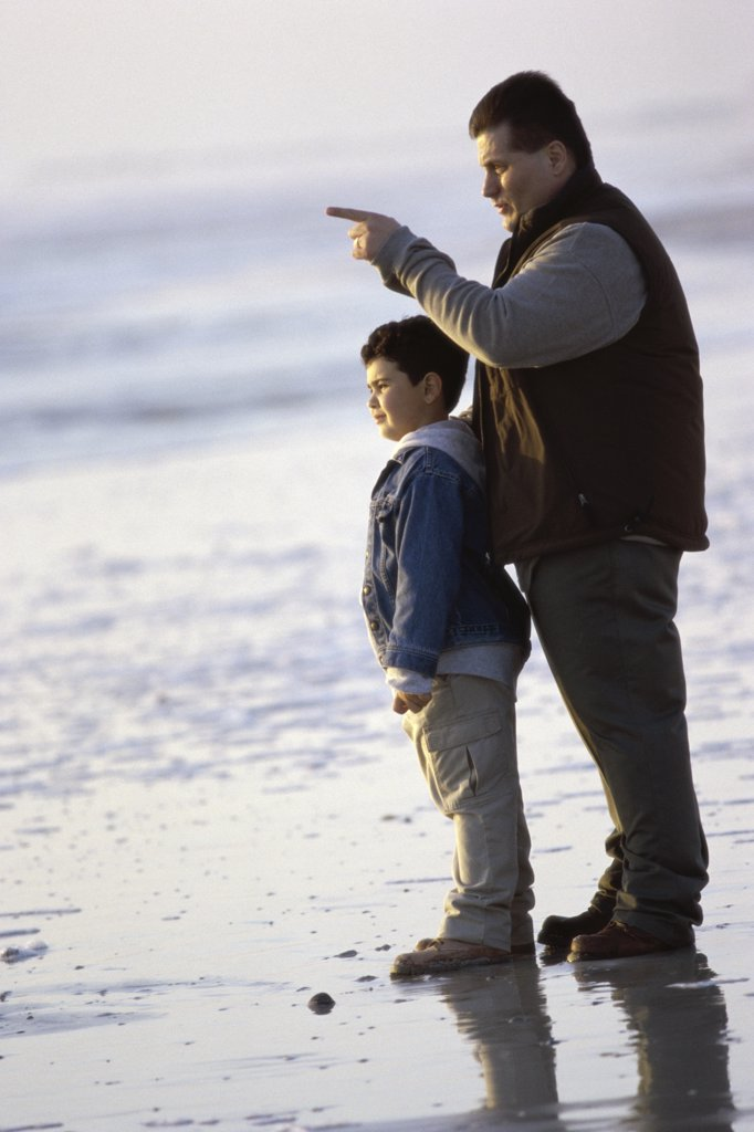 Side profile of a father and son standing on the beach : Stock Photo