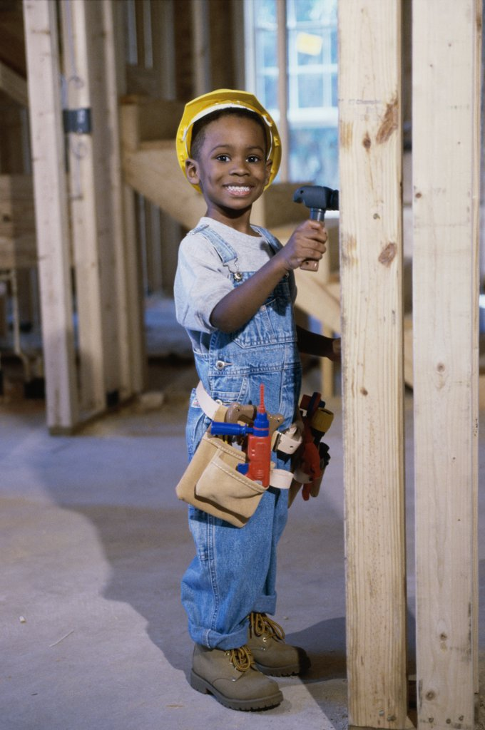 Stock Photo: 1574R-015120A Portrait of a boy dressed as a construction worker holding a toy hammer