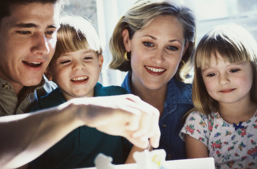 Parents and their two children smiling : Stock Photo