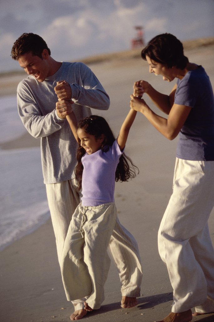 Parents swinging their daughter on the beach : Stock Photo