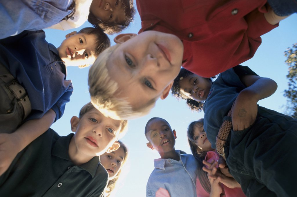 Low angle view of a group of children in a huddle : Stock Photo