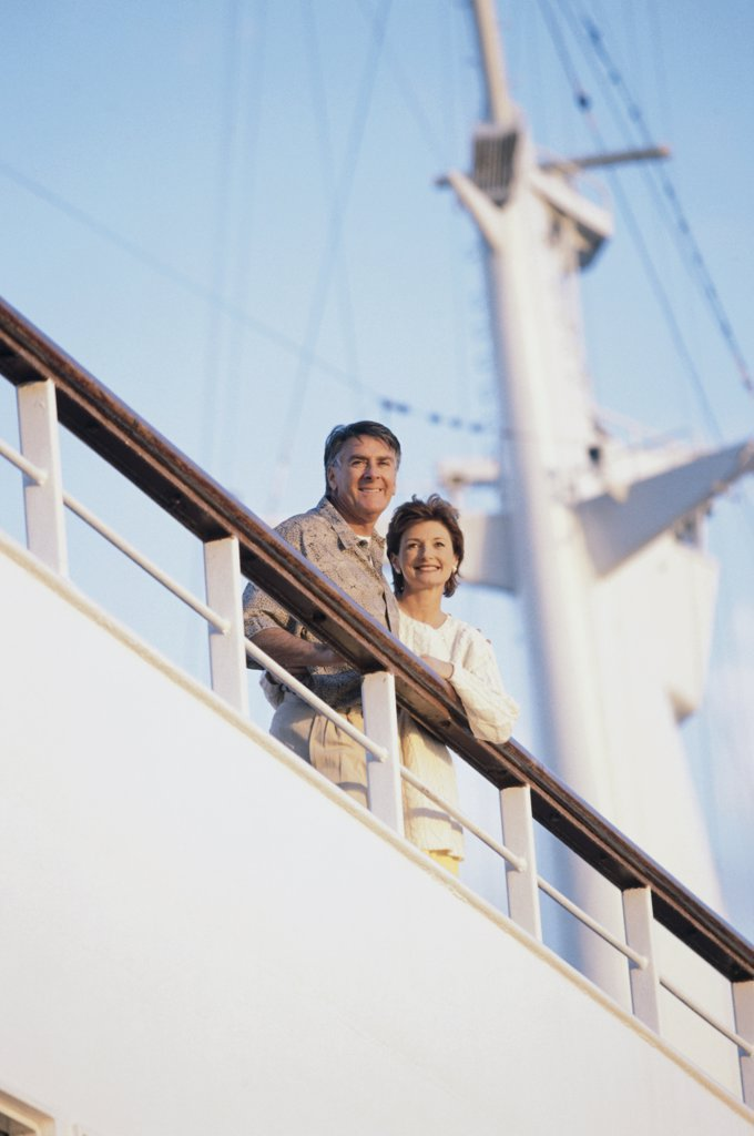 Low angle view of a mature couple standing on the deck of a cruise ship : Stock Photo