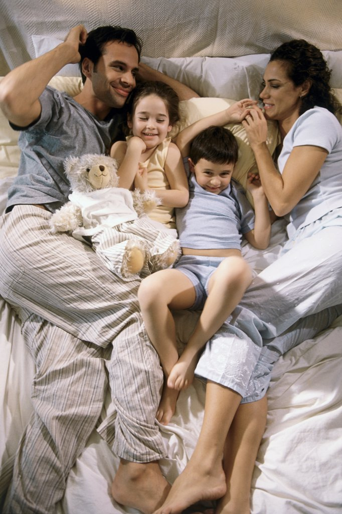 Stock Photo: 1574R-015496B High angle view of parents lying on a bed with their son and daughter