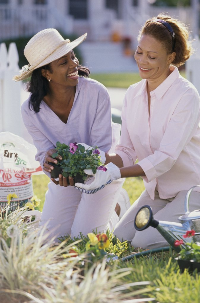 Mother gardening with her daughter : Stock Photo