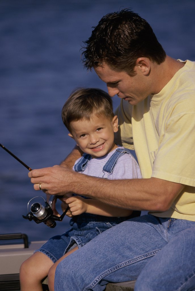 Father and son fishing from a boat : Stock Photo