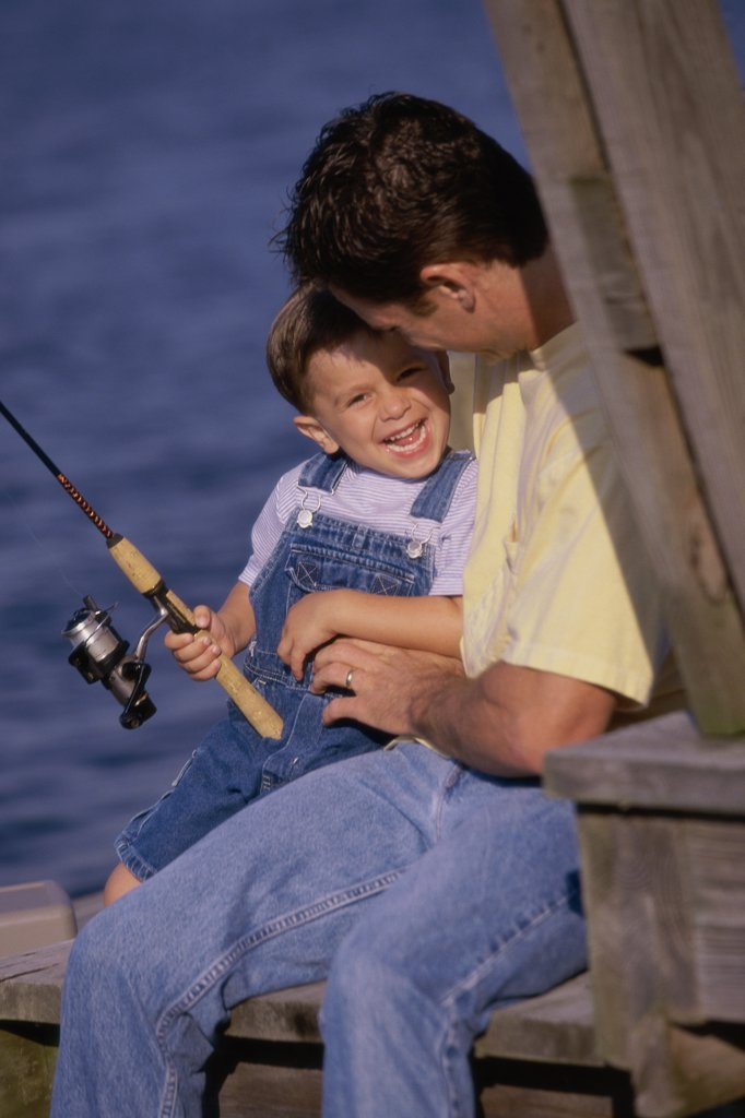 Stock Photo: 1574R-01625C Father and son fishing from a dock