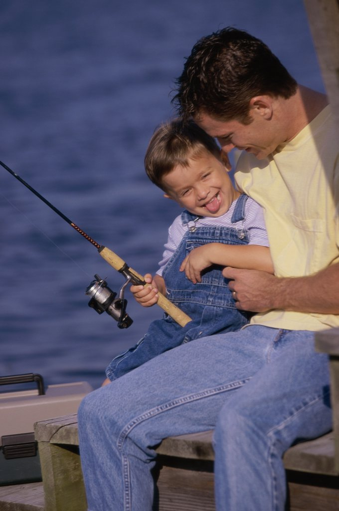 Father and son fishing from a dock : Stock Photo