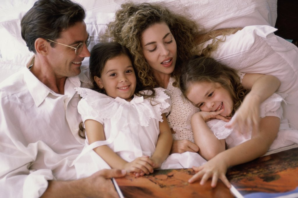 Stock Photo: 1574R-01633B Father and mother lying in bed with their two daughters