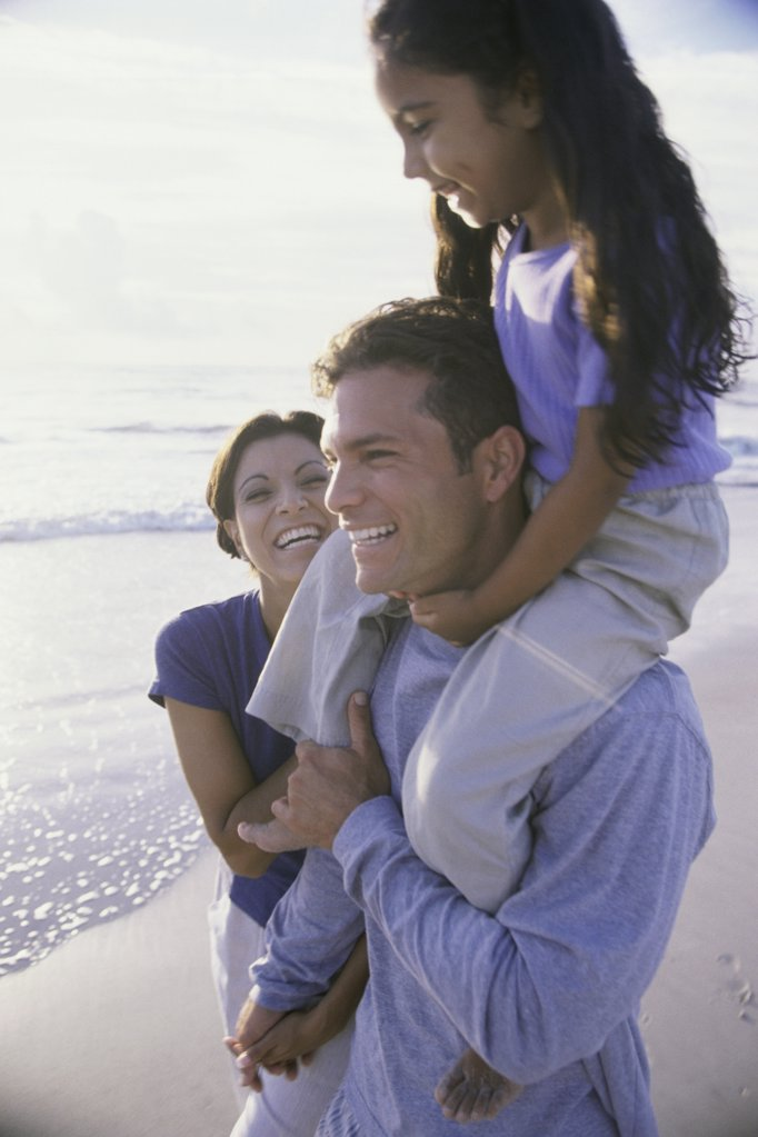 Stock Photo: 1574R-01641B Parents carrying their daughter at the beach
