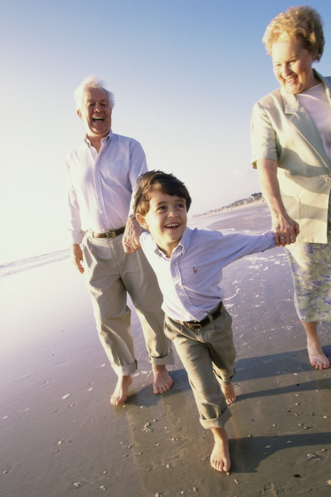 Stock Photo: 1574R-01645E Grandson running at the beach with his grandparents