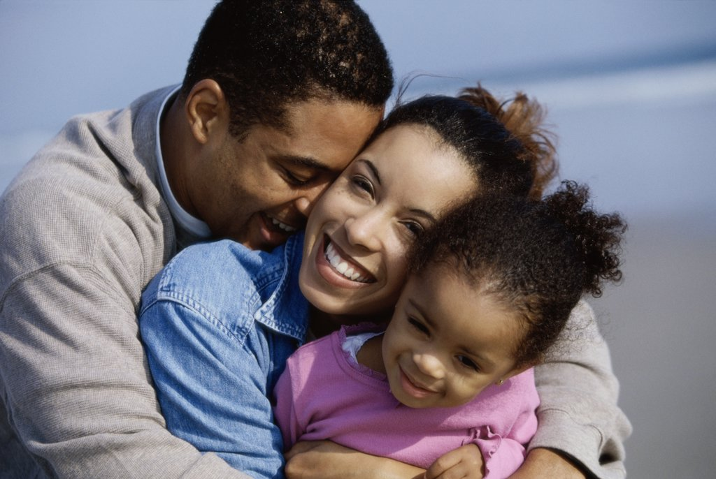 Stock Photo: 1574R-01656F Close-up of parents hugging their daughter