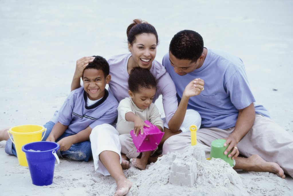 Parents playing with their son and daughter at the beach : Stock Photo