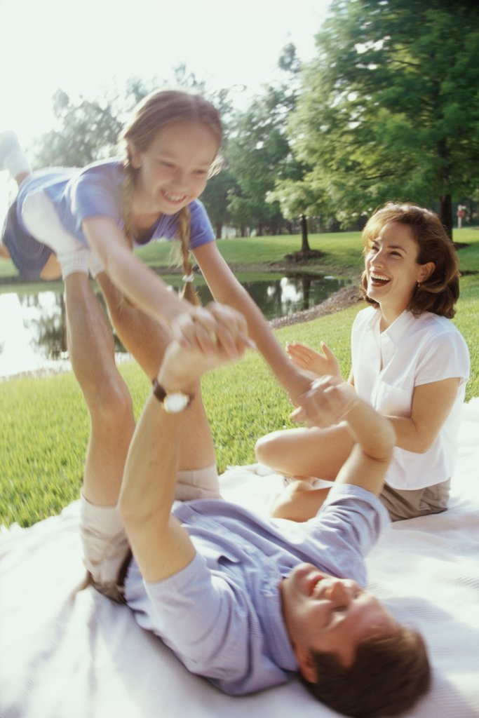 Stock Photo: 1574R-01683A Father and mother playing with their daughter on a lawn
