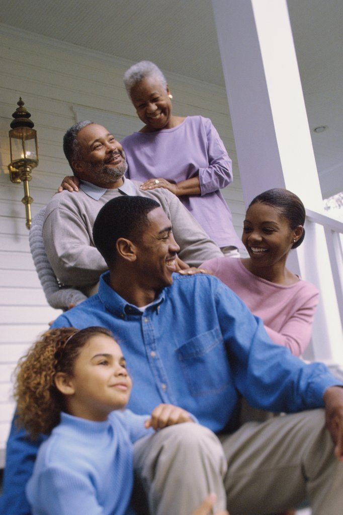 Grandparents sitting on the front porch with their son and granddaughter : Stock Photo