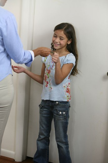 Stock Photo: 1574R-017286 Daughter taking a coin from her mother