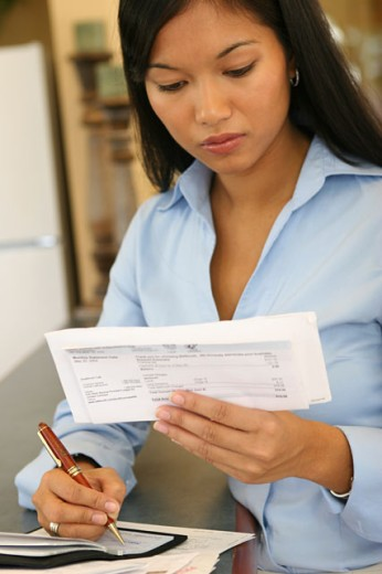 Stock Photo: 1574R-017340 Close-up of a young woman reading a bill