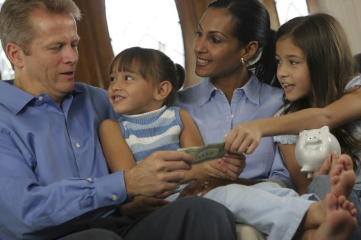 Stock Photo: 1574R-017354 Parents sitting with their two daughters holding money