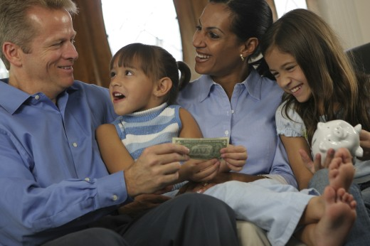 Parents sitting with their two daughters holding money : Stock Photo