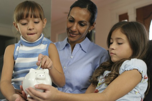 Stock Photo: 1574R-017362 Close-up of a mother looking at her two daughters inserting money into a piggy bank