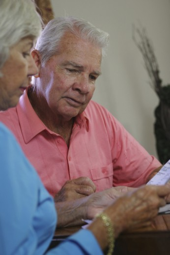 Close-up of a senior couple reading a bill : Stock Photo
