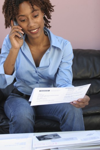Stock Photo: 1574R-017463 Close-up of a young woman holding a bill using a mobile phone