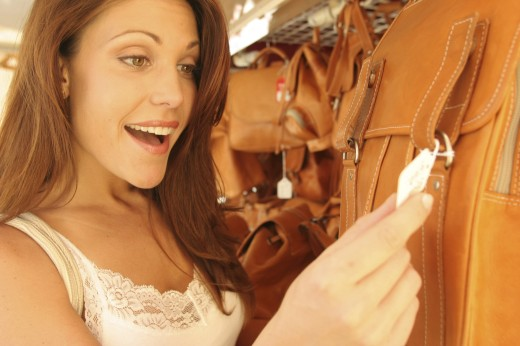 Stock Photo: 1574R-017503 Close-up of a young woman looking at the price tag on a bag in a store