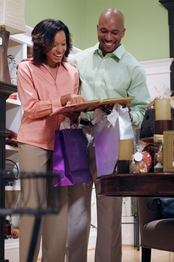 Young woman holding a book with a young man standing beside her in a store : Stock Photo
